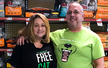Franchise owners stand in front of kibble in store