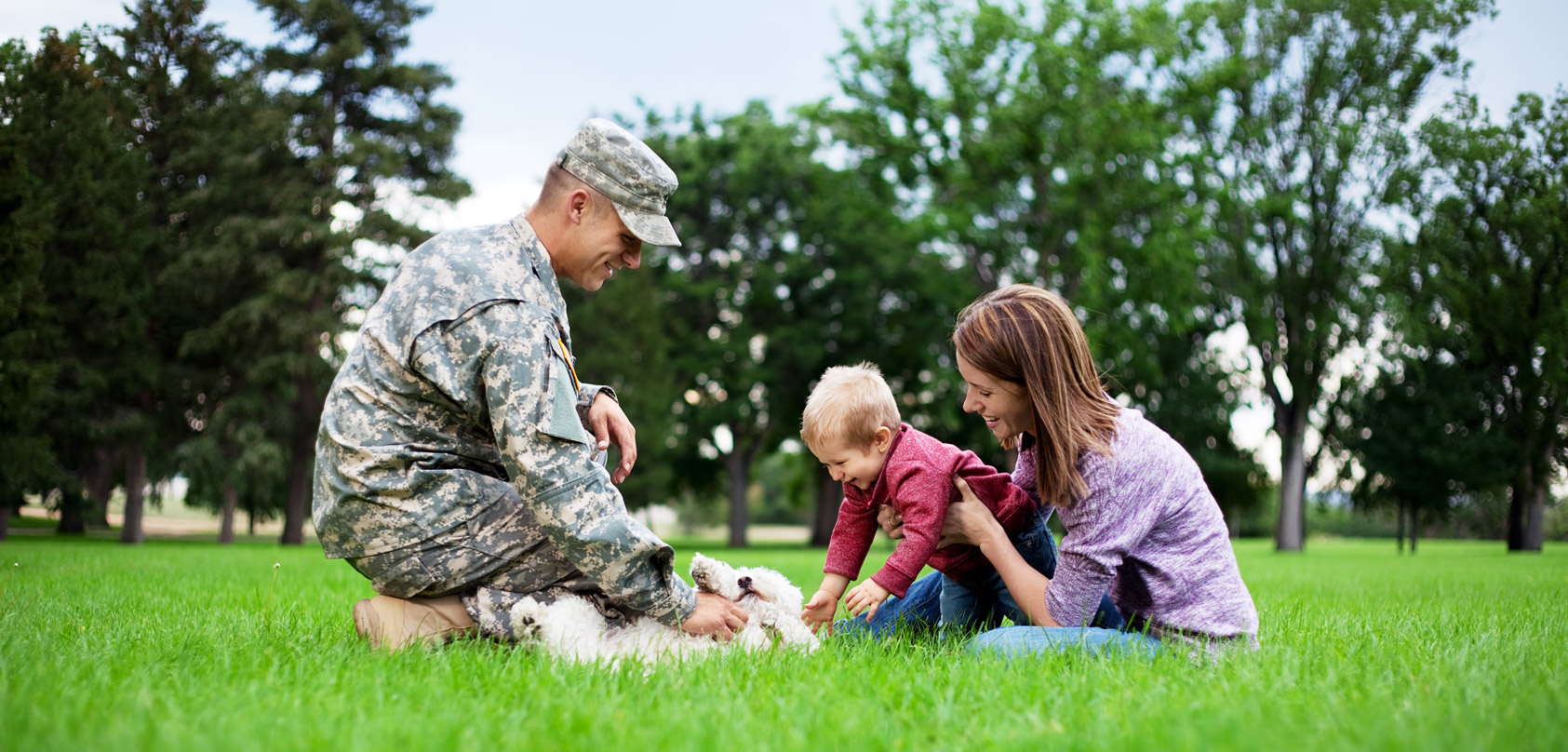 A man is dressed in a military outfit, petting his dog. His wife and small child are close by